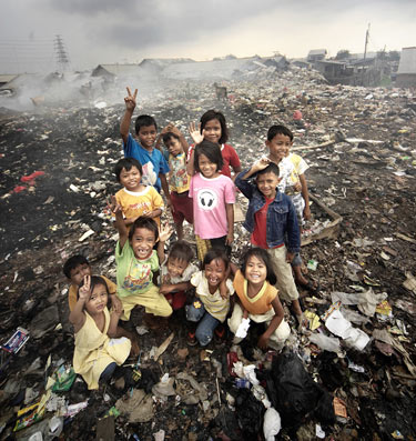 Several children stand happily on a large pile of trash at the city dump.