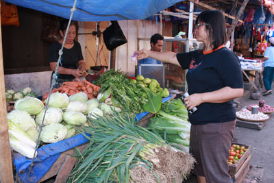 woman buying vegetables at a street market