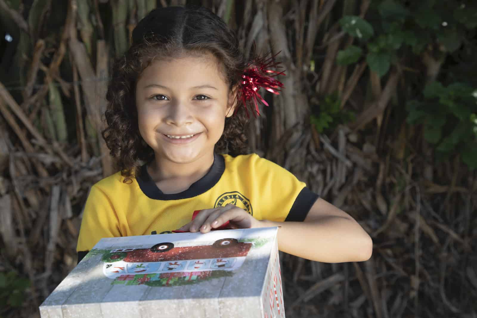 A girl in a yellow shirt holds a Christmas gift.