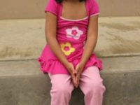 little girl dressed in pink sitting on a step