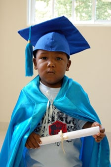 little boy in graduation cap and gown holding a diploma