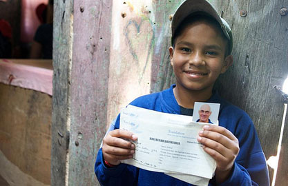 smiling boy holding a letter from his sponsor