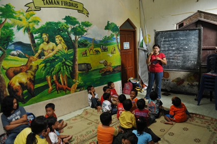 woman in a classroom instructing small children