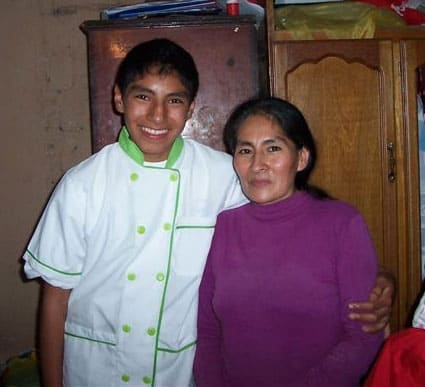 young man in white uniform standing next to older woman