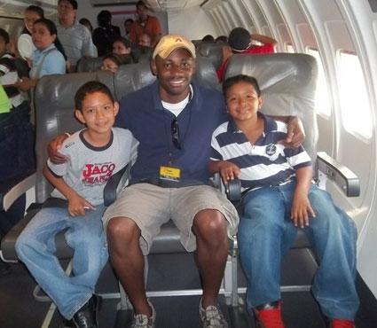 man with arms around two boys as they sit on a plane