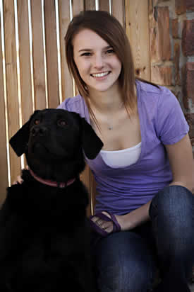 young girl sitting with black dog