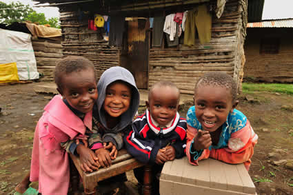 four smiling kids in front of house