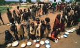 Refugee children with bowls of porridge.