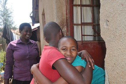 two children hugging as a smiling woman looks on