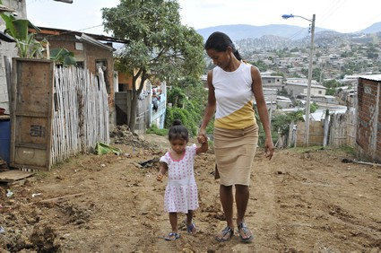 woman walking on dirt road through community holding hand of little girl