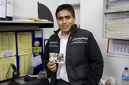 man standing in office holding a photo