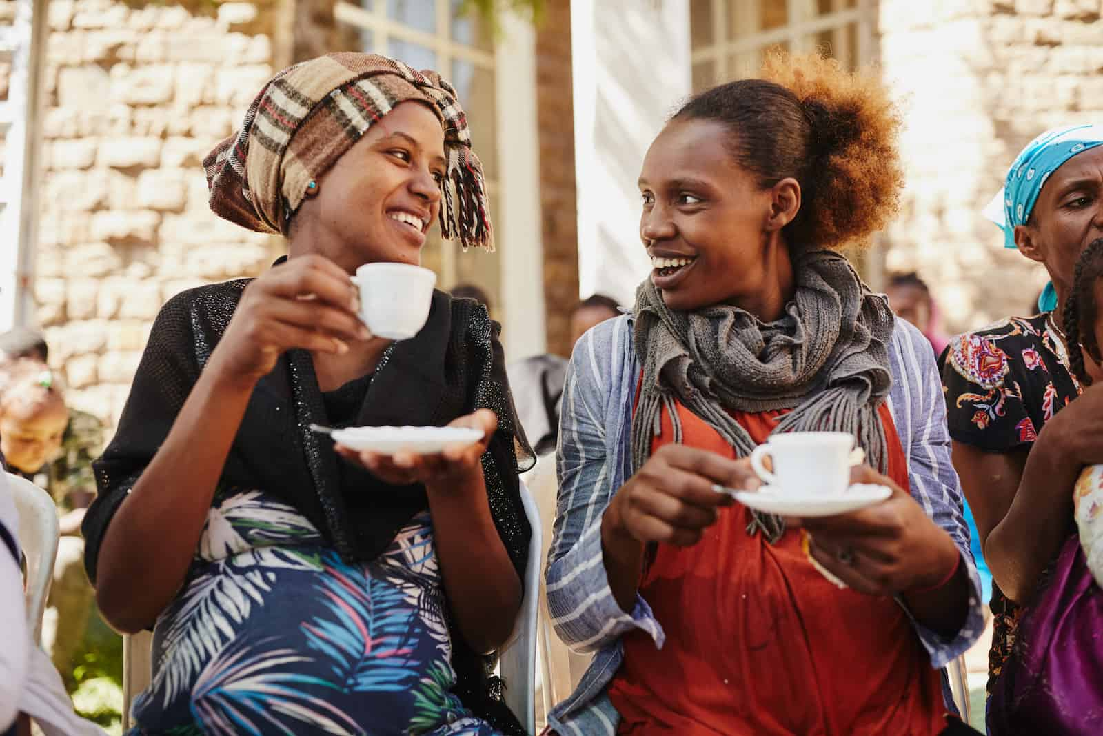 Two women drink coffee, smiling at each other.