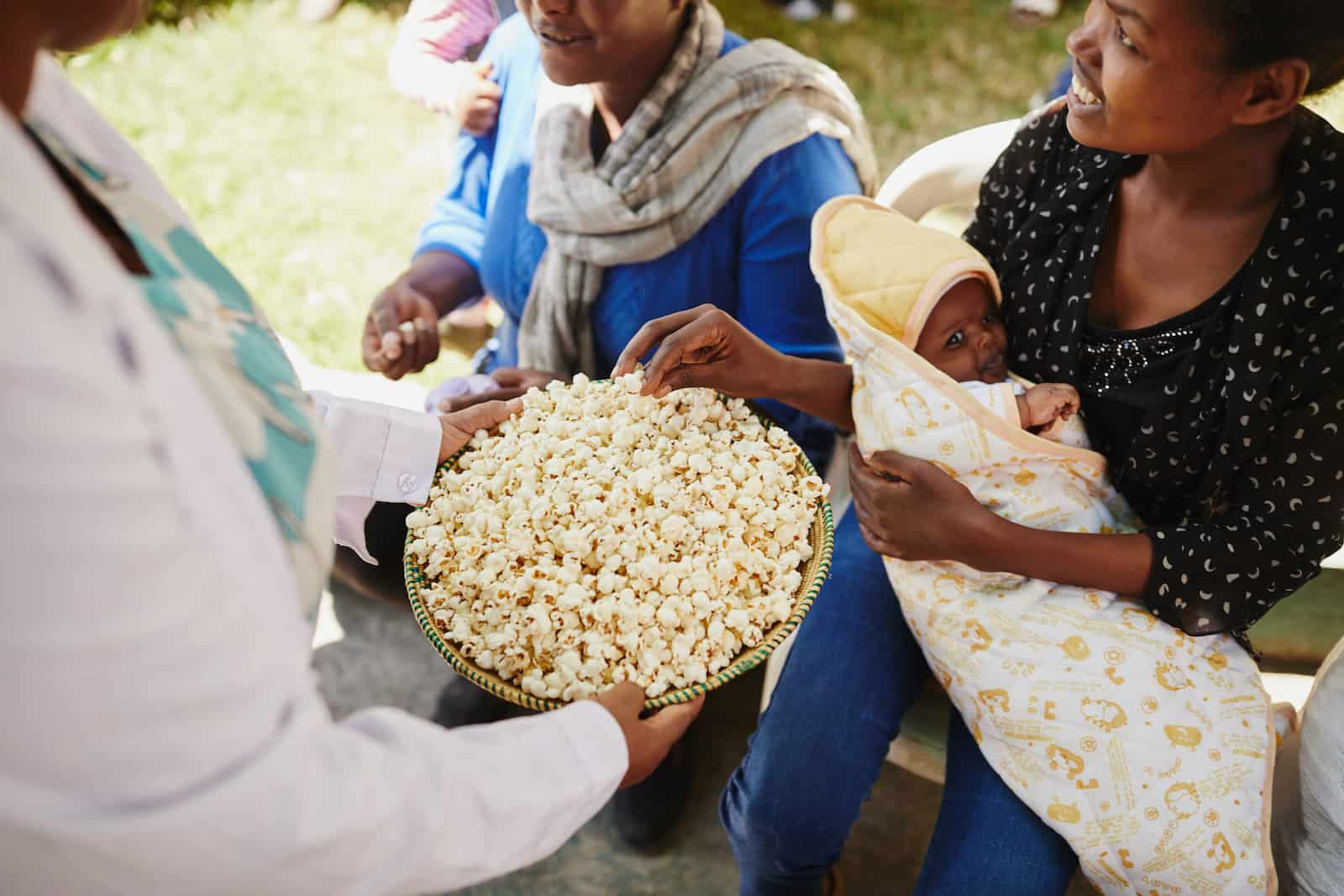 A woman holding a baby is offered a bowl of popcorn.