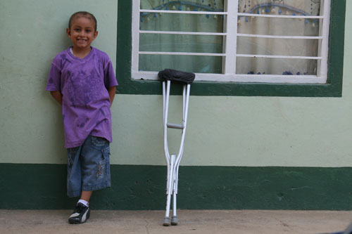 A girl stands against a wall with crutches next to her