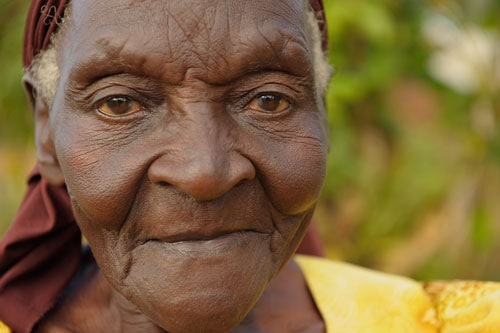 An elderly woman looks at the camera