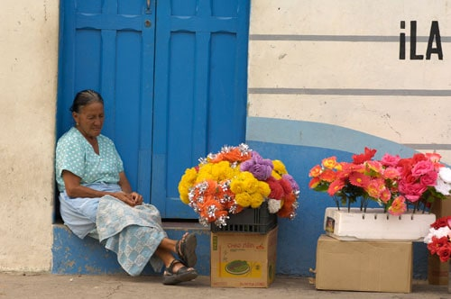 A woman sitting on the ground, selling flowers
