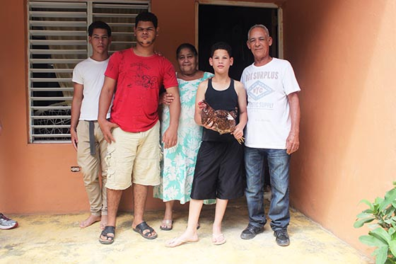Marlo is pictured on the left. Aniel, wearing red, is deaf and mute and in the Compassion program. Daniel, holding the chicken, is also deaf and mute and in the Compassion program.