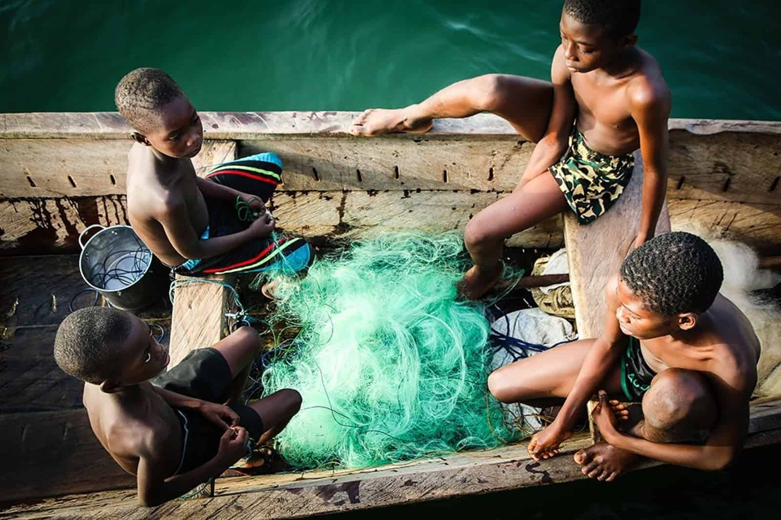 Four Ghanaian boys sit in a wooden fishing boat with green fishing net by their feet