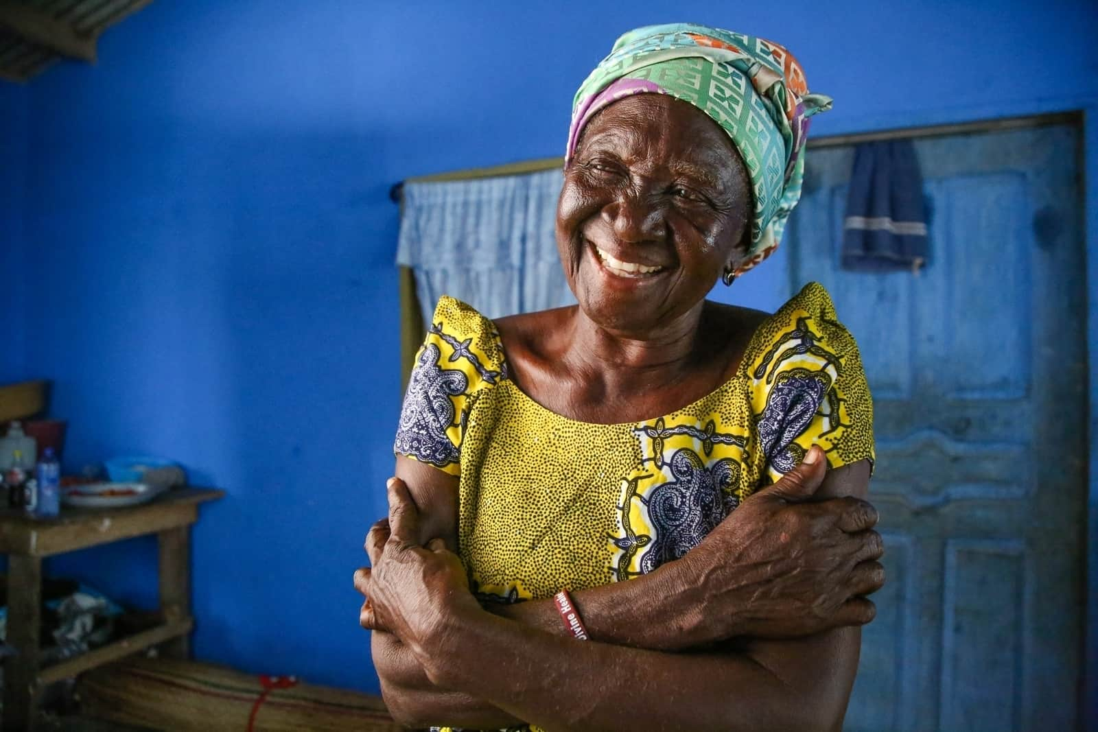 An African grandmother dressed in brightly colored clothing smiles
