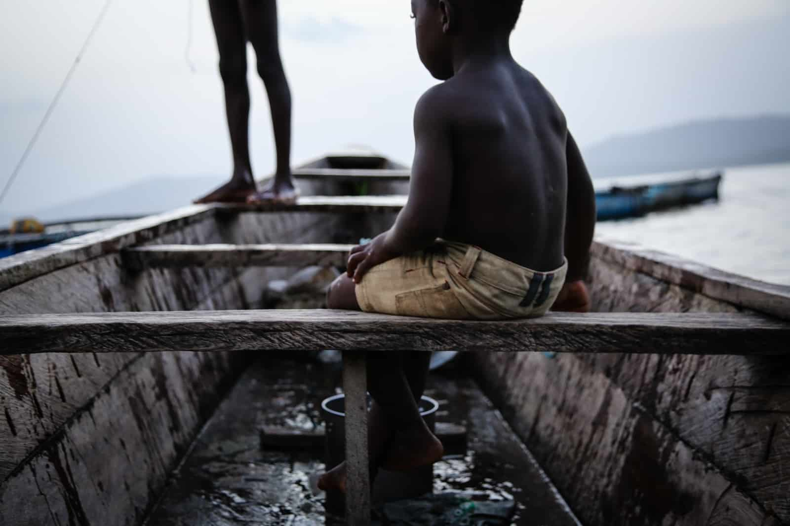 A young West African child sits in a wooden boat.