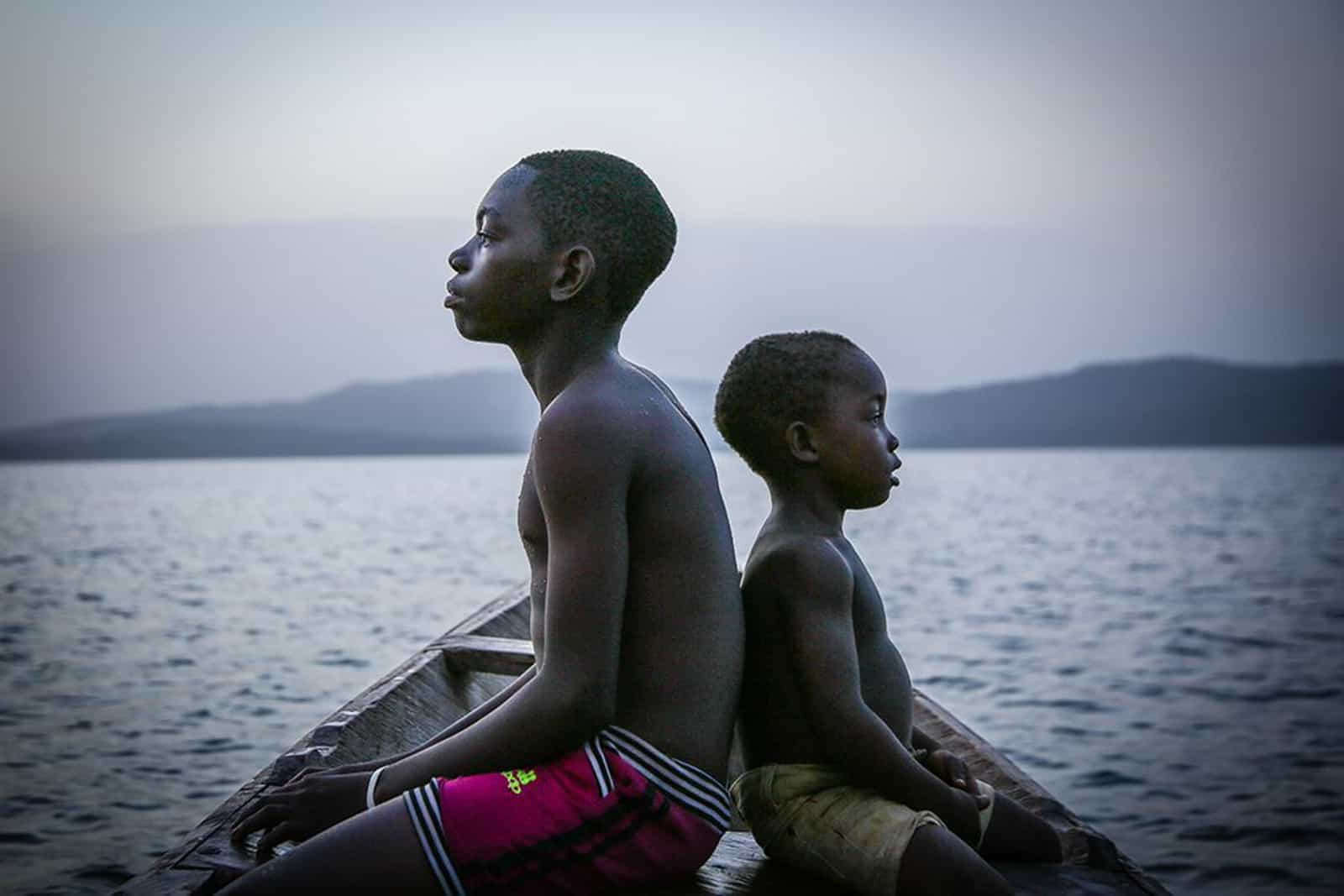 A teenage boy and a young boy sit back to back on a wooden boat floating on a lake