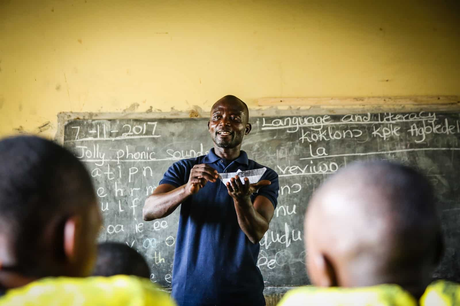 An African man wearing a blue shirt stands in front of a classroom of children, teaching them