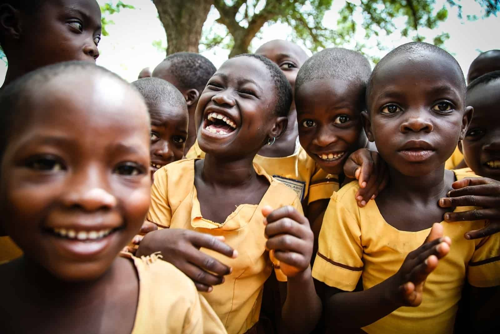 A group of Ghanaian children wearing yellow shirts smile and laugh