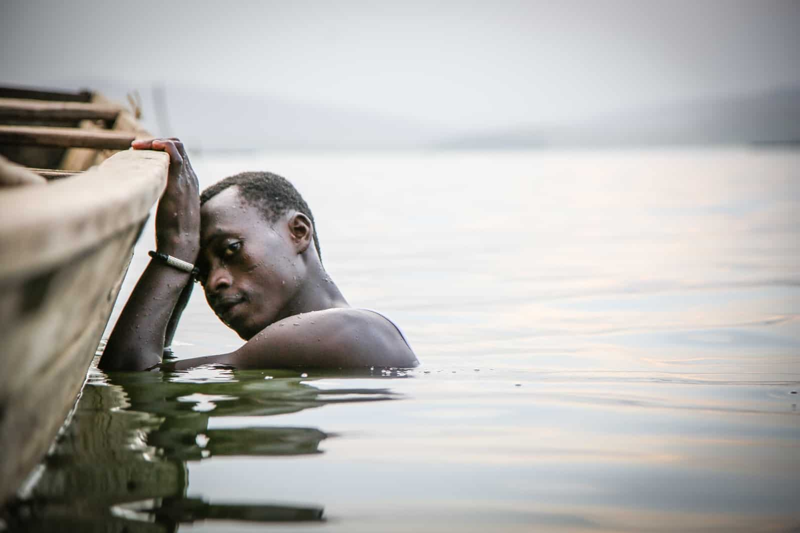 A man holds onto the side of a boat while his body is submerged in lake water