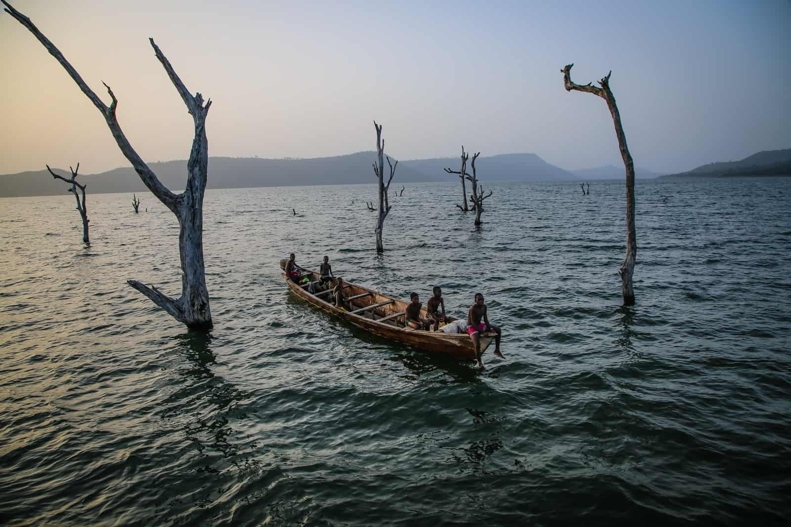 People in a fishing boat float past treetops sticking up from the lake