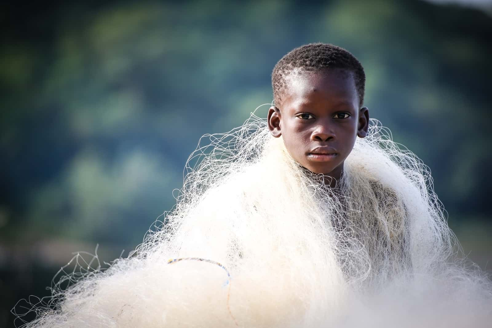 A young boy draped in tangled fishing net looks at the camera with a solemn expression
