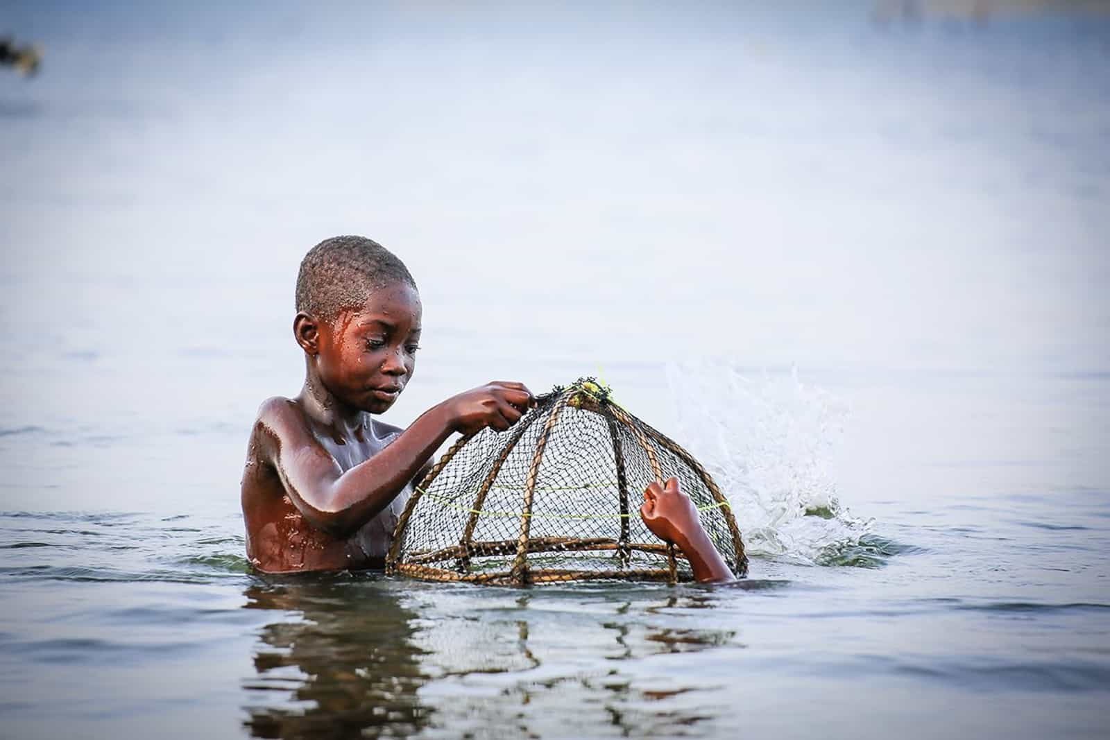 A boy holds a fishing cage into the lake water as another child dives beneath the surface