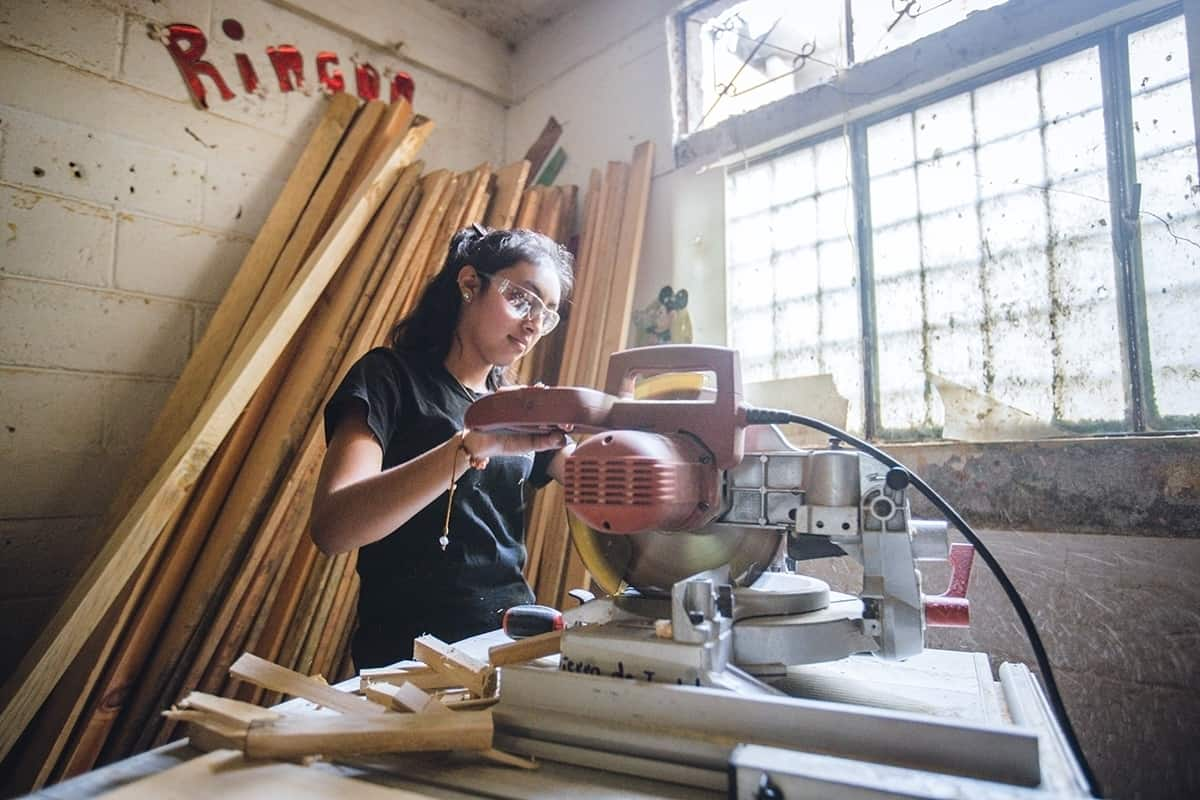 Lucerito using a table saw for some furniture she's building