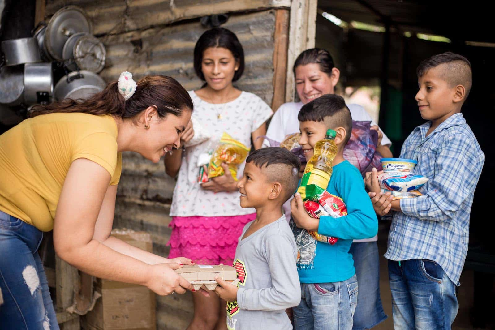 A woman leans over, handing groceries to a boy whose family has been feeding Venezuelans who fled to Colombia out of hunger.