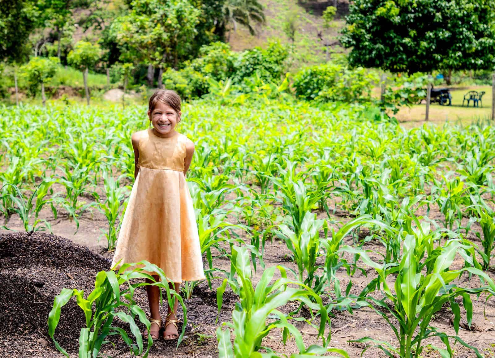 A young girl in a gold dress stands with her hands behind her back, smiling, in a large field with small corn plants growing in it.