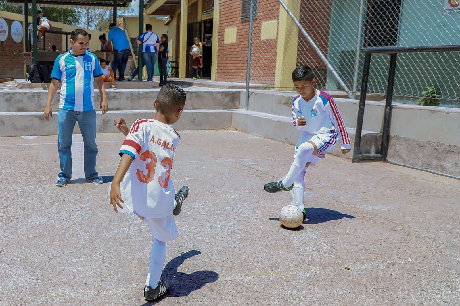Two boys in white soccer uniforms play soccer in a concrete play yard while a man in a blue and white striped shirt watches.