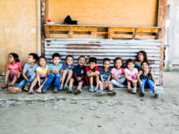 A group of 12 children sit on the ground in a line, smiling. They sit on concrete ground, in front of a corrugated metal sheet and wood wall.