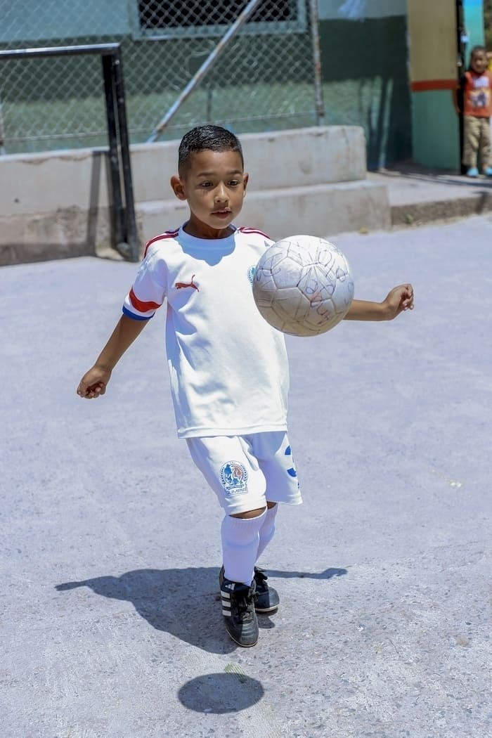 A young boy wearing a white soccer uniform bounces a soccer ball on his knee in a concrete school yard.