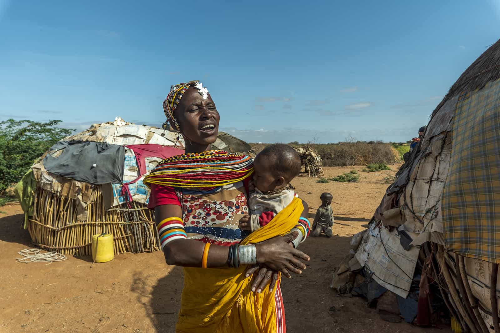A woman stands outside holding a baby to her chest, standing in front of two small round huts.