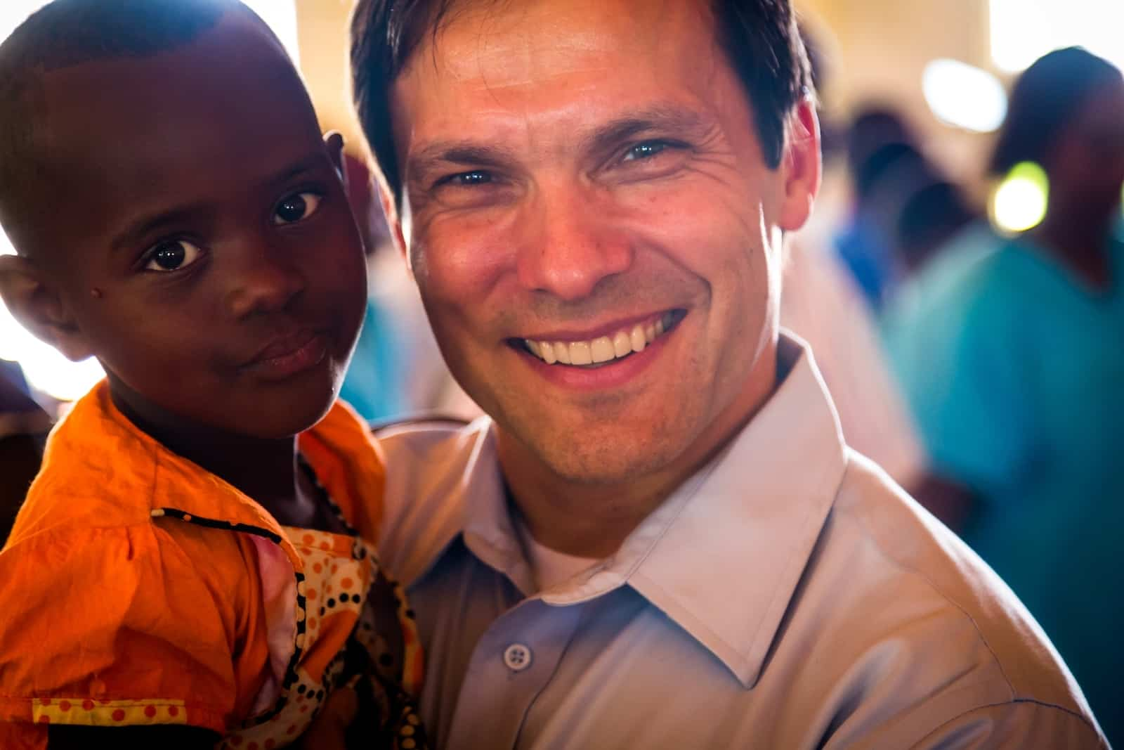 An Easter Message of hope form our President, pictured smiling and holding a young Rwandan girl wearing an orange dress.