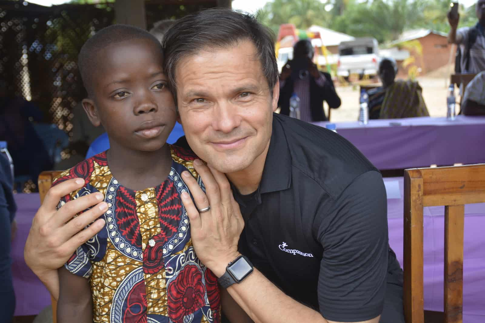 """A man, Santiago """"Jimmy"""" Mellado, wearing a black shirt that says """"Compassion"""" stoops down and puts his arms around a young boy wearing a yellow and red Togolese shirt."""