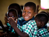 A boy in Burkina Faso wearing a green and blue checked shirt holds his hands together in praying while smiling at the camera. He is in a classroom surrounded by other children praying.