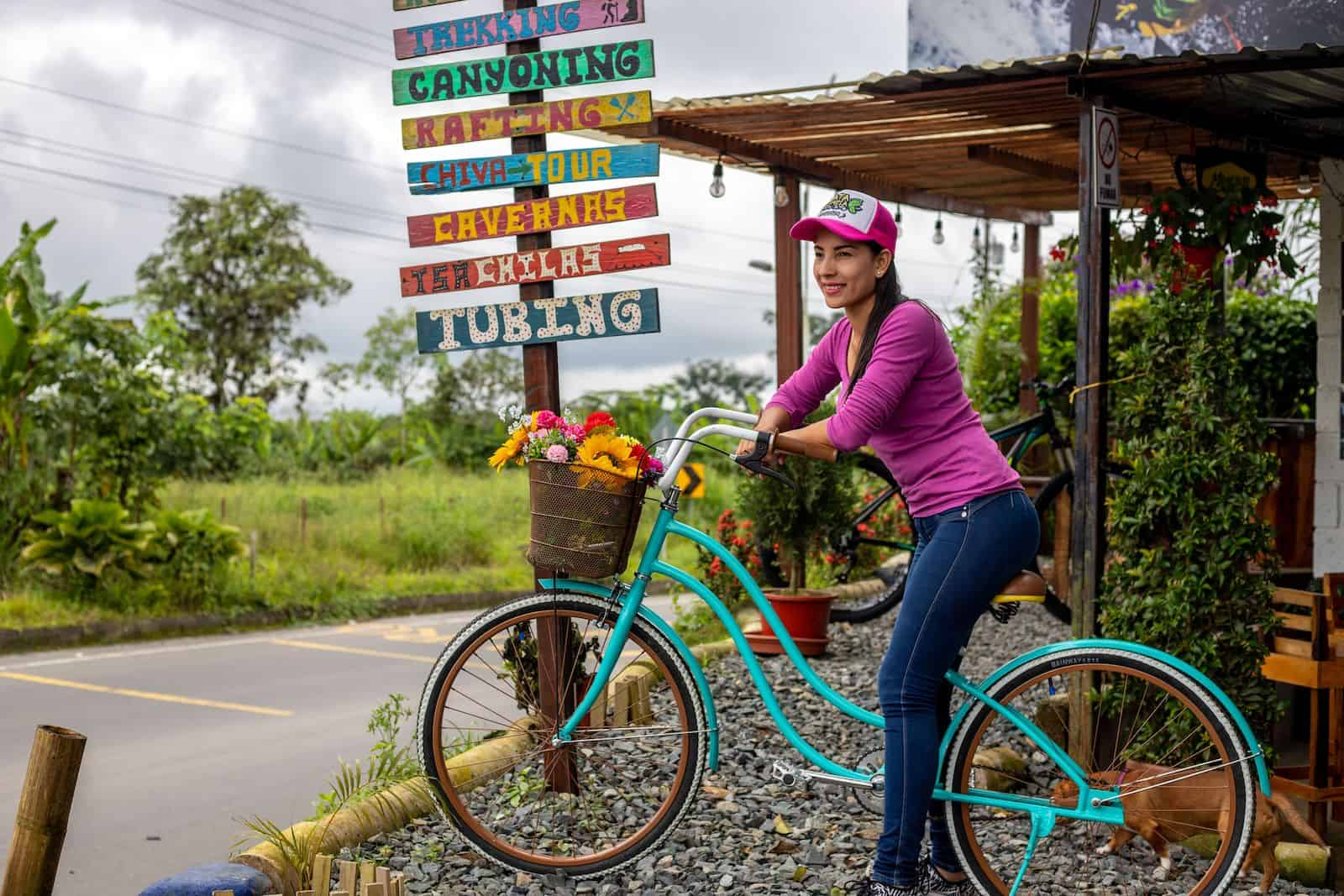 """A woman in a pink shirt, jeans and a baseball cap sits on a turquoise bike on a roadside, with a sign behind her that reads, """"Trekking, Canyoning, Rafting, Tubing,"""" etc."""