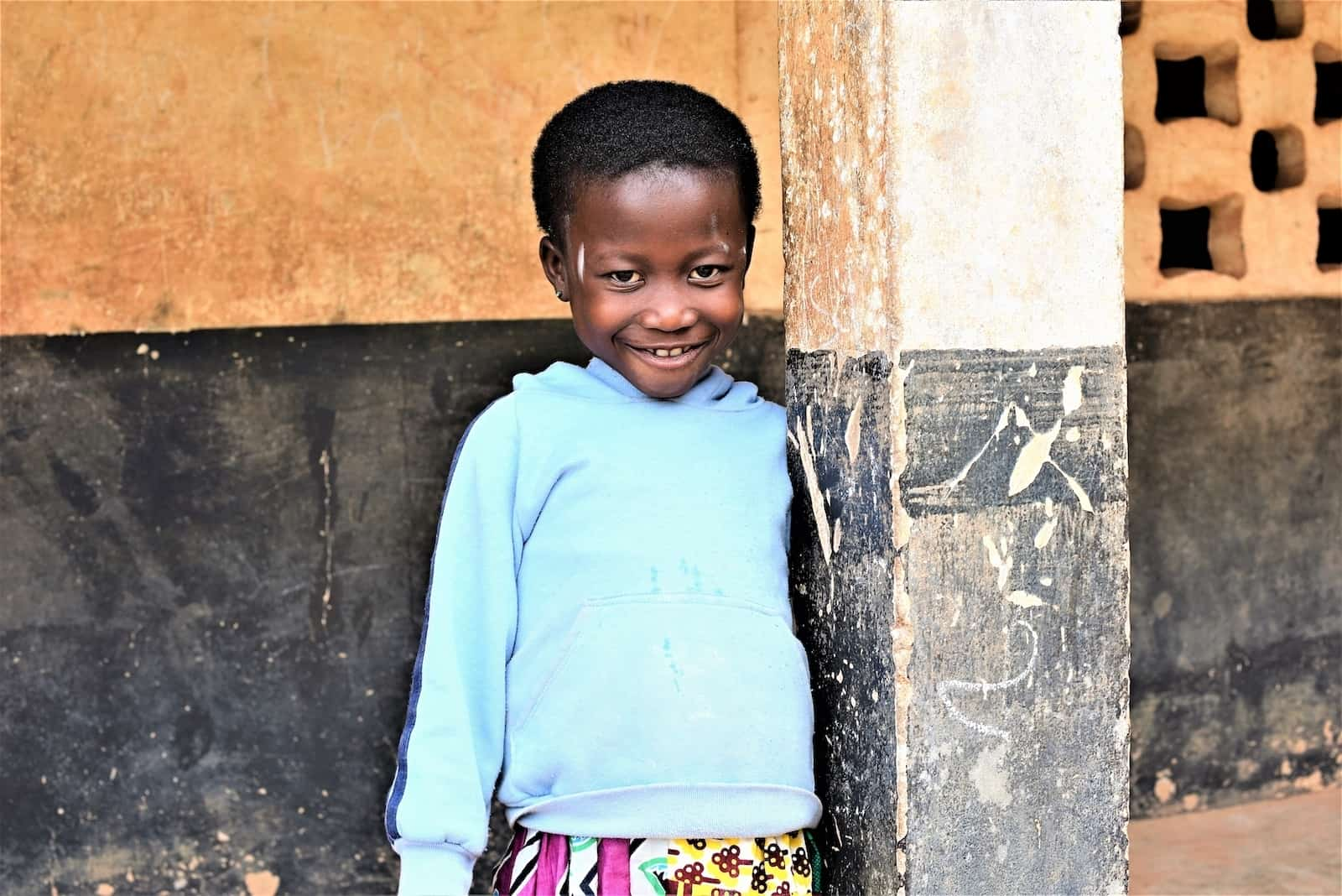 A girl who was trapped inside by a Ghana superstition wears a light blue sweatshirt and patterned dress smiles, standing next to a column in front of a black and white wall.