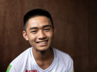 A teenage boy wearing a white shirt smiles at the camera. He sits in front of a brown background.