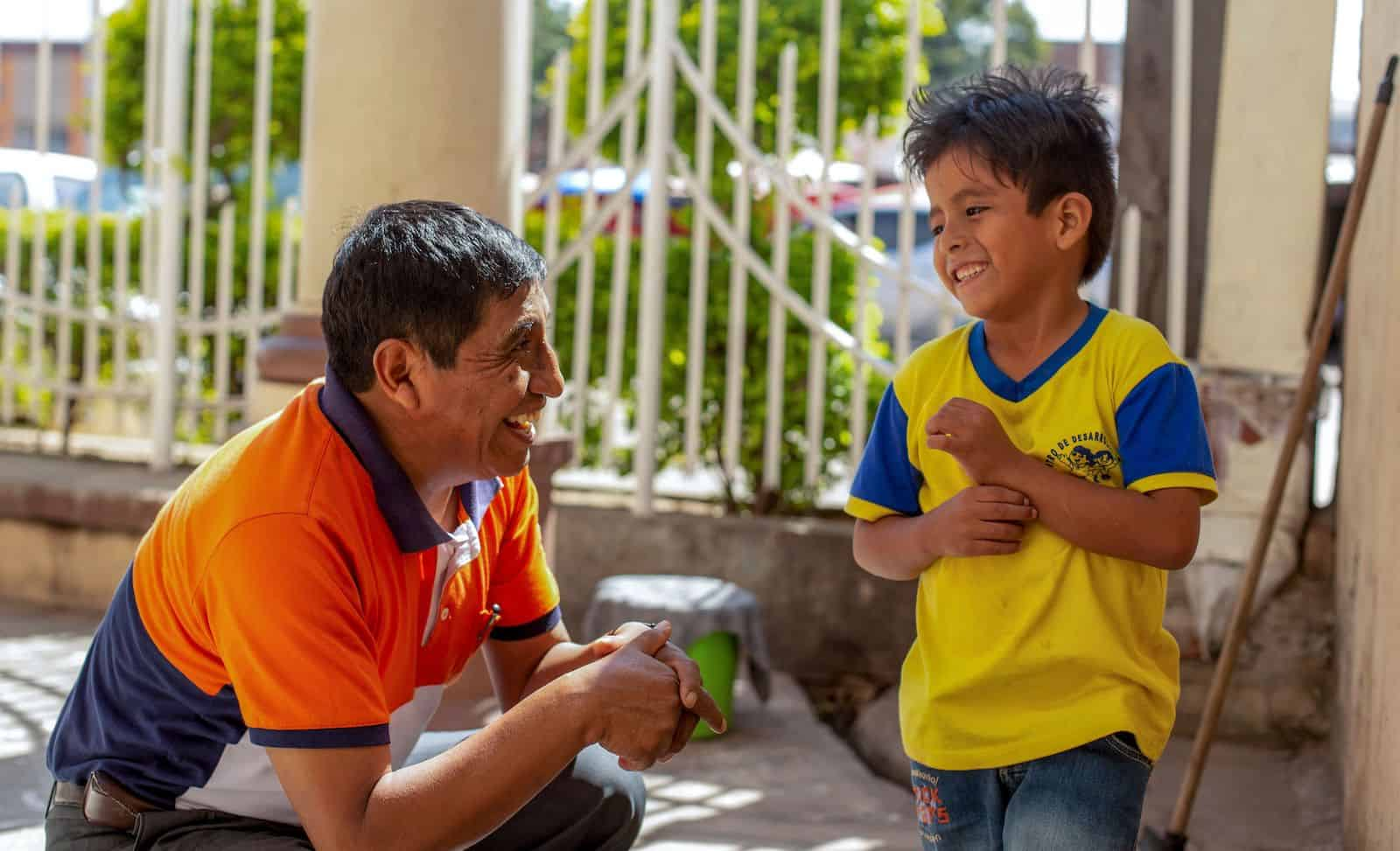 A man in an orange shirt kneels next to a boy in a yellow shirt, talking to him in.