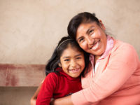 A woman in a coral colored sweater hugs a little girl in a red shirt.