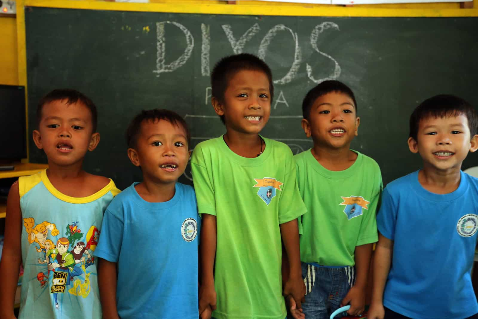A group of five young boys stand, smiling, in front of a chalk board.