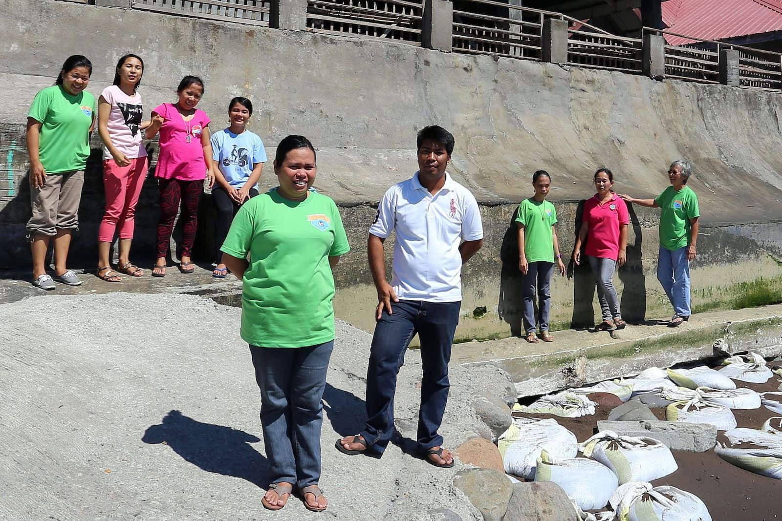A group of people stand outside a concrete church building, wearing jeans and T-shirts.