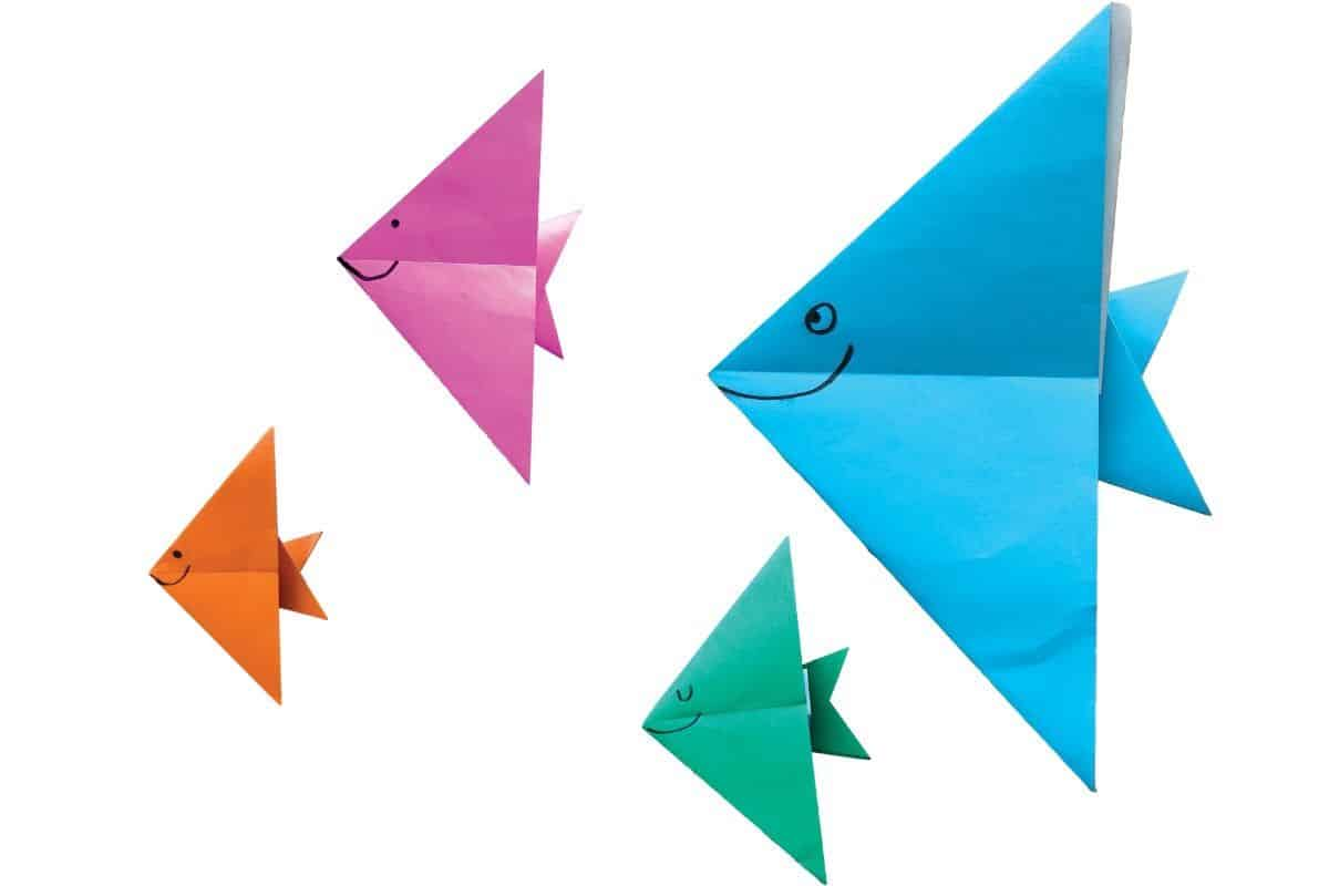 Four origami fishes in blue, green, orange and pink paper.