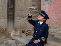 A girl wearing a navy blue pilot's uniform and cap sits on a sidewalk, holding a toy airplane up into the sky, looking at it.